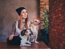 En stilfull tattoed blond kvinnlig i t-skjorta och jeans omfamnar två gulliga hundkapplöpning Royaltyfri Foto