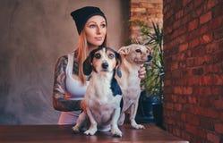 En stilfull tattoed blond kvinnlig i t-skjorta och jeans omfamnar två gulliga hundkapplöpning Arkivfoton