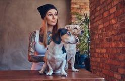 En stilfull tattoed blond kvinnlig i t-skjorta och jeans omfamnar två gulliga hundkapplöpning Arkivbild