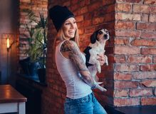 En stilfull tattoed blond kvinnlig i t-skjorta och jeans rymmer en gullig hund Royaltyfri Foto