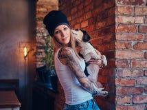 En stilfull tattoed blond kvinnlig i t-skjorta och jeans rymmer en gullig hund Royaltyfria Foton