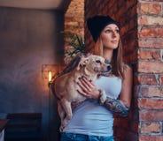 En stilfull tattoed blond kvinnlig i t-skjorta och jeans rymmer en gullig hund Arkivfoto