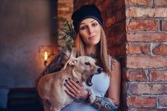 En stilfull tattoed blond kvinnlig i t-skjorta och jeans rymmer en gullig hund Arkivfoton