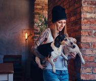En stilfull tattoed blond kvinnlig i t-skjorta och jeans rymmer två gulliga hundkapplöpning Royaltyfri Fotografi