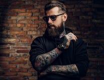 En stilfull tatuerad grabb i en svart hoodie och solglasögon Studiofoto mot tegelstenväggen arkivfoton