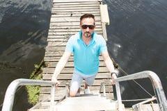 En stilig affärsman på semester med yachter på skeppsdocka och träpirbakgrund Man i solglasögon som laddering upp arkivbild