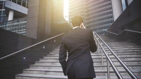 En stilig affärsman som går upp trappa och har telefonkonversation fotografering för bildbyråer