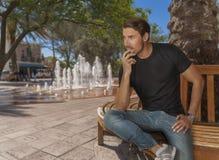 En stilig färdig man sitter på en bänk på staden parkerar vid vattenspringbrunnen royaltyfri fotografi