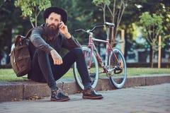 En stilig hipsterhandelsresande med ett stilfullt skägg och tatuering på hans iklädda tillfälliga kläder och hatt för armar med e royaltyfri bild