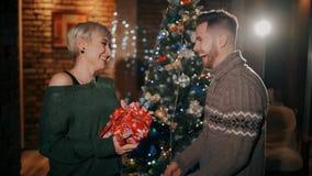 En stilig man ger en lycklig flicka per julgåva i deras brunn-planlagda vardagsrum lager videofilmer