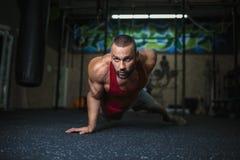 En stilig man med en muskulös kropp på en suddig bakgrund Den sexiga muskelmannen gör en liggande armhävning i idrottshallen spor Royaltyfri Foto