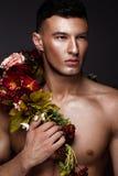 En stilig man med en nakna torso, bronssolbränna och blommor på hans kropp Fotografering för Bildbyråer