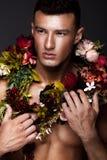 En stilig man med en nakna torso, bronssolbränna och blommor på hans kropp Arkivbilder