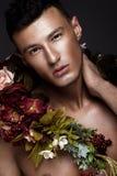 En stilig man med en nakna torso, bronssolbränna och blommor på hans kropp Arkivfoto