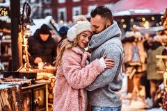 En stilig man och en charmig flickakel och tycka om spendera tid tillsammans, medan stå på vintermässan på a royaltyfri foto