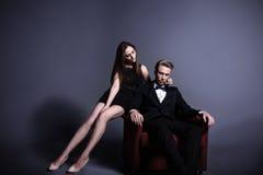 En stilig man och en härlig kvinna i mörkret Royaltyfri Bild