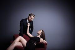 En stilig man och en härlig kvinna i mörkret Fotografering för Bildbyråer