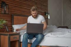 En stilig man sitter på sängkanten med en dator i hans händer arkivbild
