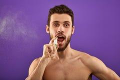 En stilig man som besprutar andedräkt för att förnya hans mun royaltyfria bilder