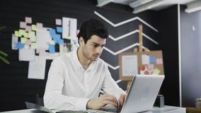 En stilig mankontorschef som ser till kameran som sitter i hans arbetsplats stock video