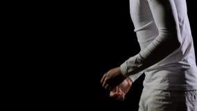 En stilig manlig gymnast i vit g?r akrobatiska jippon p? en svart bakgrund i ultrarapid, rotation och bl?ddrar mening lager videofilmer