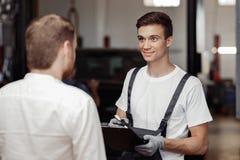 En stilig mekaniker talar till hans klient om det gjorda arbetet royaltyfri bild