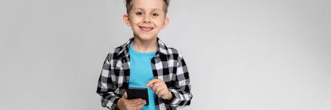En stilig pojke i en plädskjorta, blå skjorta och jeans står på en grå bakgrund Pojken rymmer en telefon arkivbilder