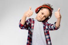 En stilig pojke i en plädskjorta, grå skjorta och jeans står på en grå bakgrund En pojke i röd hörlurar Pojken för pojke Arkivbild