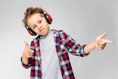 En stilig pojke i en plädskjorta, grå skjorta och jeans står på en grå bakgrund En pojke i röd hörlurar Pojken för pojke Arkivfoto