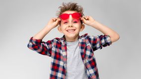 En stilig pojke i en plädskjorta, grå skjorta och jeans står på en grå bakgrund En pojke i röd solglasögon Pojken för pojke Arkivbild