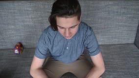 En stilig pojke som en tonåring i desperation sitter på en grå soffa royaltyfria bilder