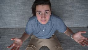 En stilig pojke som en tonåring i desperation sitter på en grå soffa arkivfoto