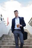 En stilig ung affärsman som går för att arbeta med hans portfölj och ett kaffe Royaltyfria Bilder
