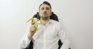 En stilig ung man ser kameran och äter en ny banan stock video