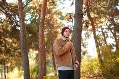 En stilig ung man som går i höstskogen arkivfoton