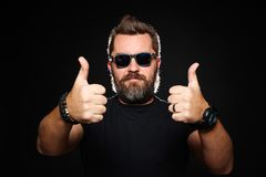 En stiligt stark man med en stilfull frisyr och skägg visar två tummar upp i studion på en svart bakgrund Med kopiera utrymme royaltyfri bild