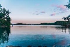 En stilla sjö på solnedgången fotografering för bildbyråer
