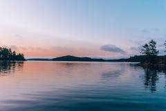 En stilla sjö på solnedgången arkivbild