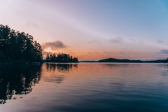 En stilla sjö på solnedgången royaltyfri bild
