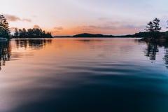En stilla sjö under solnedgång royaltyfri bild