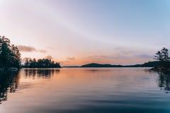 En stilla sjö under solnedgång royaltyfri fotografi