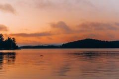 En stilla sjö under solnedgång royaltyfria bilder
