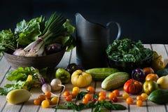 En stillebenplats av en skottpengar av ny jordbruksprodukter inklusive tomater, rovor, grönkål, peppar och gurkor arkivfoto