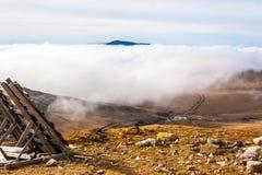 En stillsam bergplats med det molnräkningen och staketet på en kulle Royaltyfria Bilder