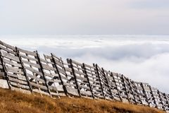 En stillsam bergplats med det molnräkningen och staketet på en kulle Fotografering för Bildbyråer