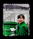 En stolpe 1984-2009 - kvinna som postar en bokstav, serie, circa 2009 Royaltyfri Foto