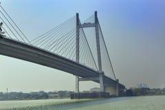 En stor arkitektur av den jätte- bron med blå livlig himmel och grönt blått vatten fotografering för bildbyråer