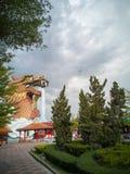 En stor drakebyggnad i trädgården, medan himlen är nära att regna royaltyfri fotografi