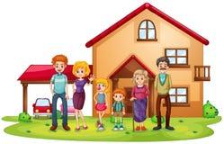 En stor familj framme av ett stort hus Arkivbild