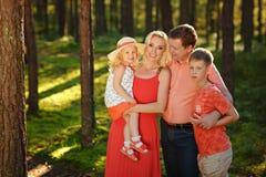 En stor familj: mamman farsa och deras behandla som ett barn leende i skogen i t Arkivfoto